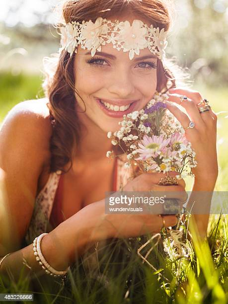Lächelnd hippie-Mädchen in einem park holding wild blumen