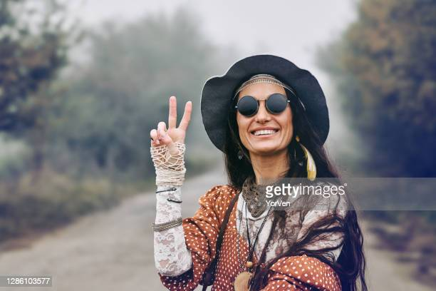 smiling hippie woman giving peace sign - 20th century stock pictures, royalty-free photos & images