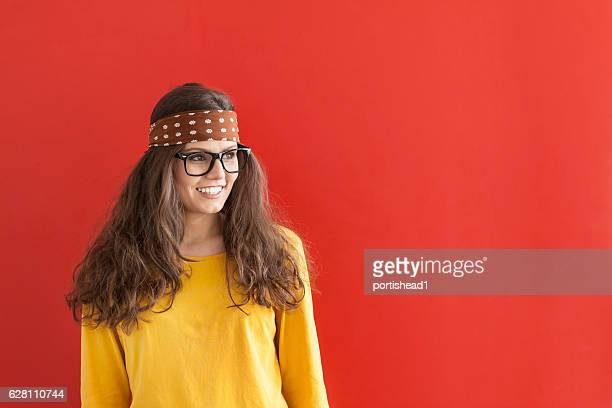 Smiling hippie woman on red background