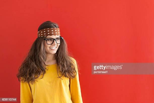 smiling hippie woman on red background - cinta de cabeza fotografías e imágenes de stock
