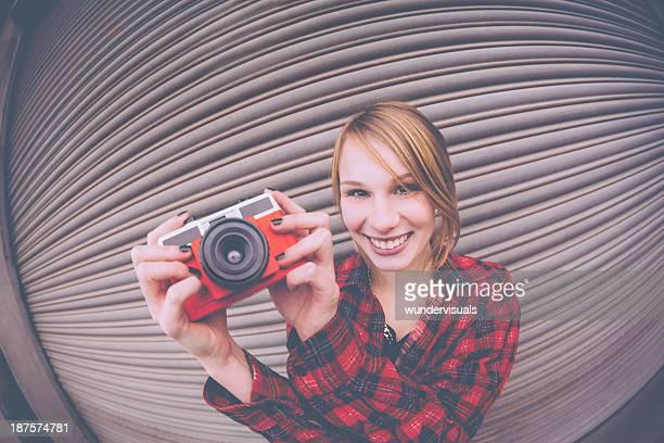 カメラに笑うのヒップスターを抱える少女