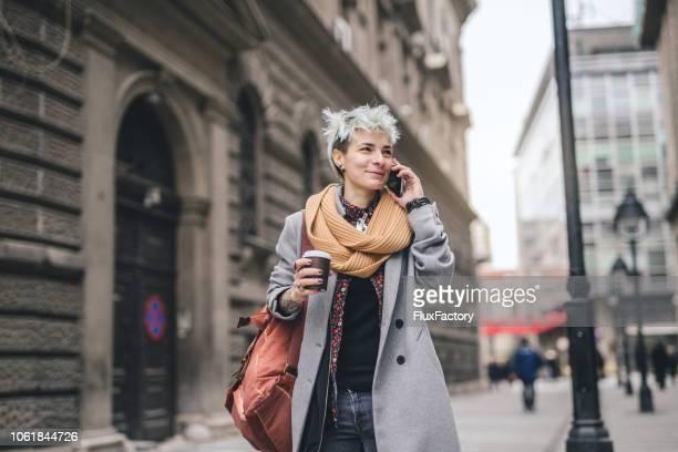 lachende hipster meisje praten op een mobiele telefoon - genderblend stockfoto's en -beelden