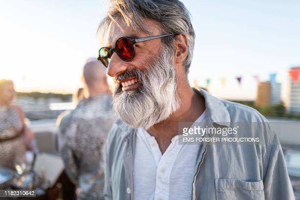 smiling hipster man on a rooftop party in munich - hipster person stock-fotos und bilder