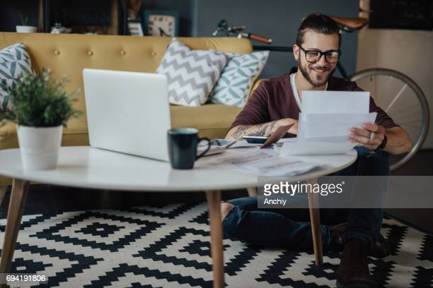 Smiling Hipster sitting on the floor and studying for the exam in the living room