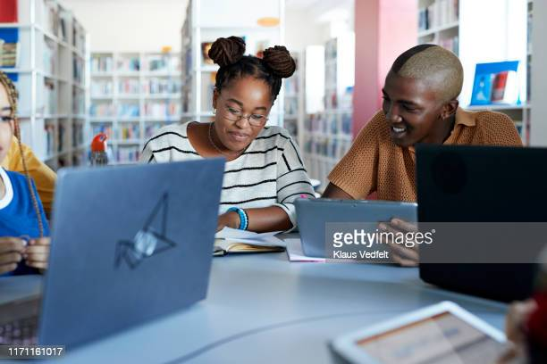 smiling hipster student with female friend at desk - online community stock pictures, royalty-free photos & images