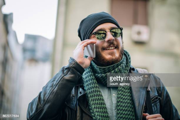 smiling hipster talking on the phone - biker jacket stock photos and pictures