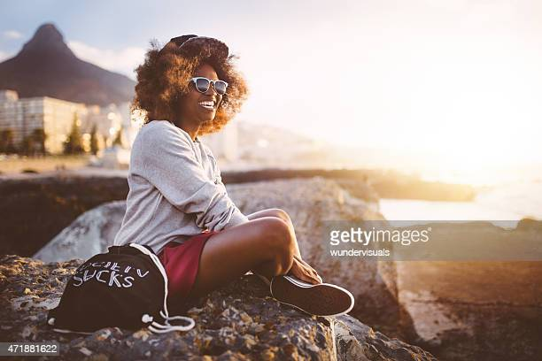 Smiling hipster teen girl sitting by herself at the beach
