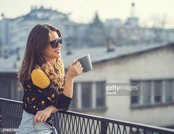 Lächelnd hipster Frau, die einen Kaffee auf der Terrasse.