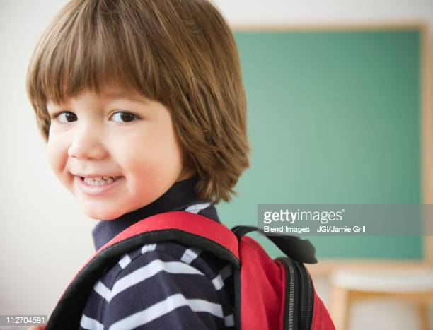 Smiling Hispanic boy wearing backpack