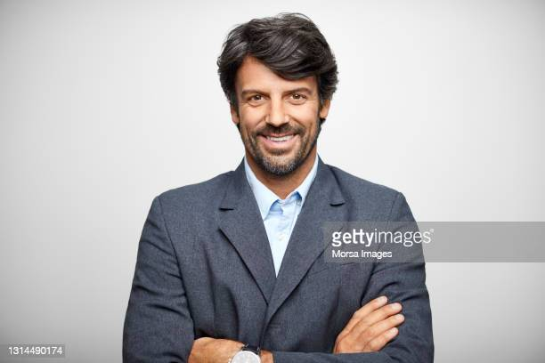 smiling hispanic businessman against gray background - waist up stock pictures, royalty-free photos & images