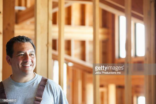 Smiling Hispanic construction worker in unfinished room