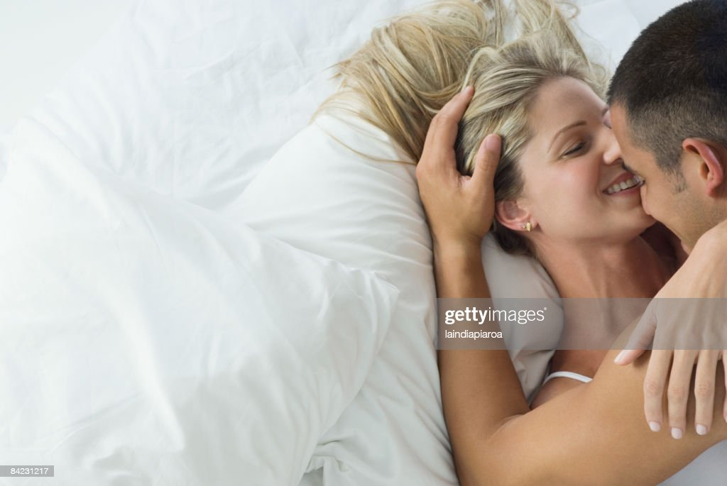 Smiling Hispanic couple laying in bed : Stock Photo