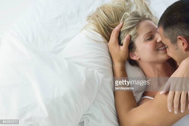 smiling hispanic couple laying in bed - sex stock photos and pictures