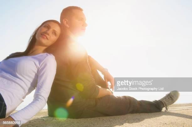 smiling hispanic couple sitting on beach - 背中合わせ ストックフォトと画像