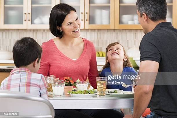 Smiling Hispanic family eating dinner