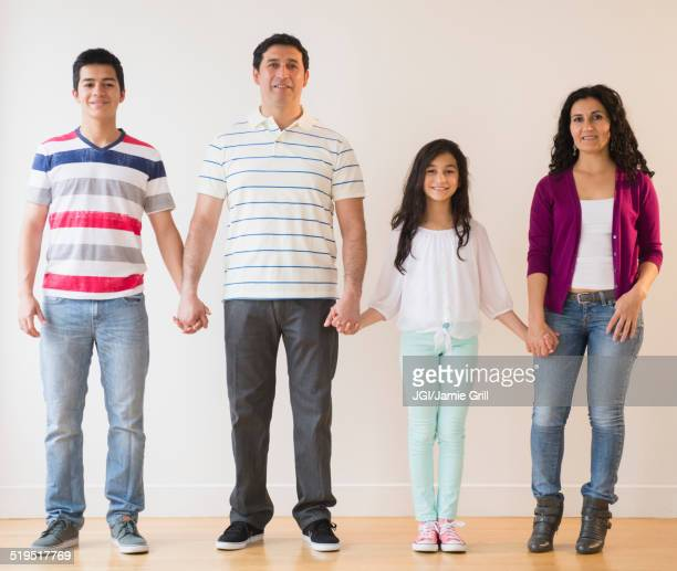Smiling Hispanic family holding hands