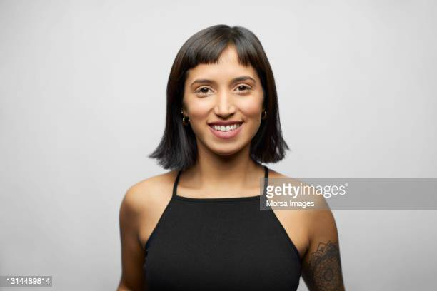 smiling hispanic female against gray background - waist up stock pictures, royalty-free photos & images