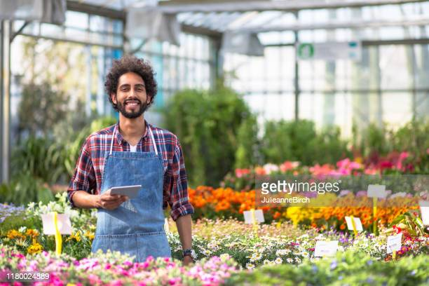 smiling hispanic garden center assistant with digital tablet - garden center stock pictures, royalty-free photos & images