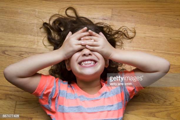 Smiling Hispanic girl covering her eyes on floor