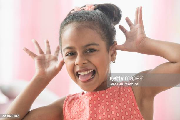 smiling hispanic girl making a face - human tongue stock pictures, royalty-free photos & images