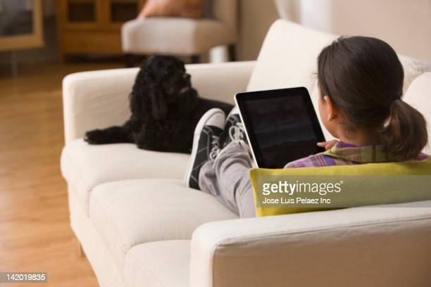 Smiling Hispanic girl using digital tablet