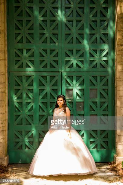 Smiling Hispanic girl wearing gown near green wall