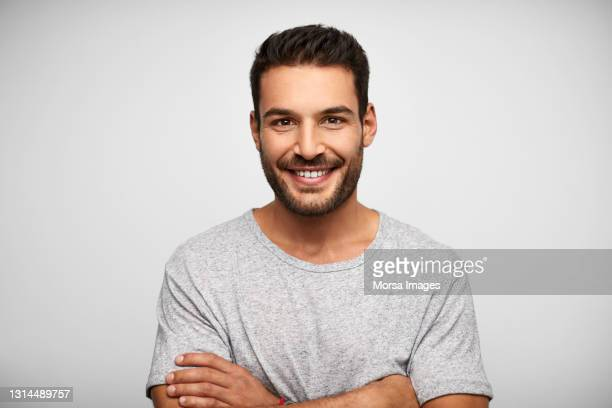 smiling hispanic man against white background - 20 29 anos imagens e fotografias de stock