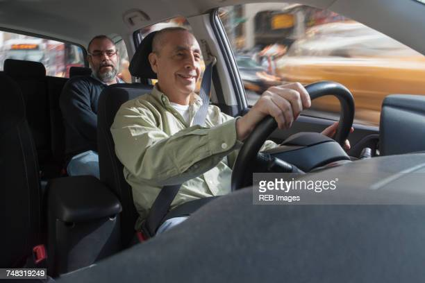 Smiling Hispanic man driving car with passenger