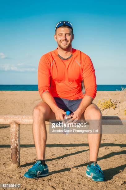 Smiling Hispanic man sitting on railing at beach