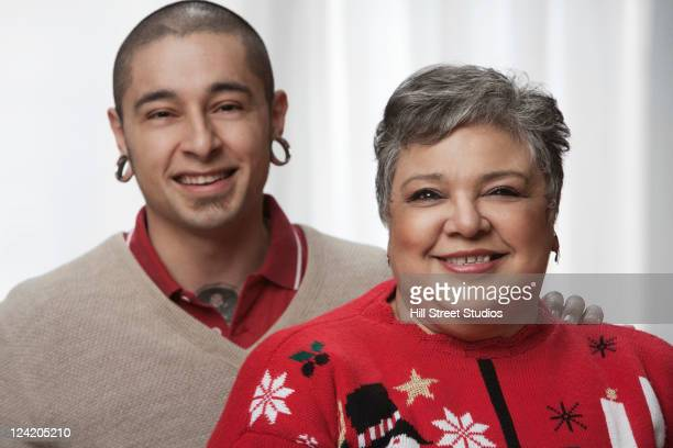 smiling hispanic man standing with mother - earlobe stock photos and pictures