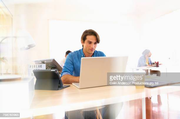 Smiling Hispanic man using laptop in office