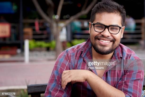 Smiling Hispanic man with beard sitting on bench