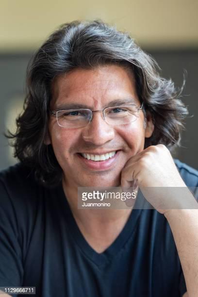 smiling hispanic mature man looking at the camera - homem moreno imagens e fotografias de stock