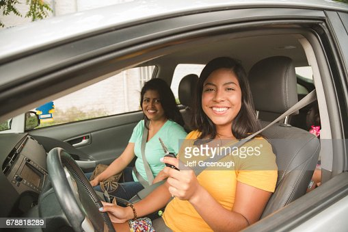 Smiling Hispanic mother and daughter posing in car