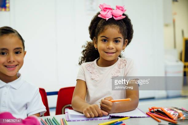 smiling hispanic schoolgirls drawing in the classroom - hair bow stock pictures, royalty-free photos & images