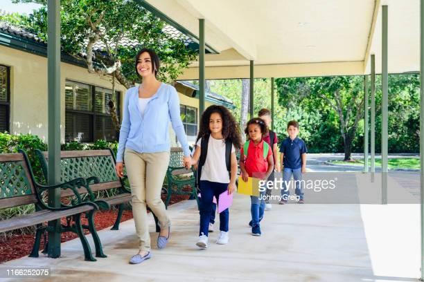 professora e estudantes latino-americanos de sorriso que andam ao ar livre - courtyard - fotografias e filmes do acervo