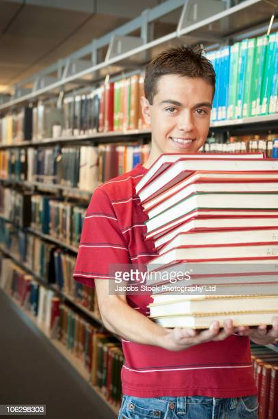 Smiling Hispanic student carrying stack of books in library