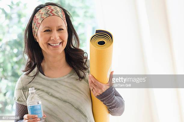 Smiling Hispanic woman holding exercise mat and water bottle