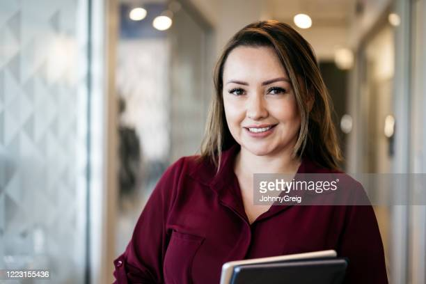 smiling hispanic woman in mid 30s at work - 35 39 years stock pictures, royalty-free photos & images