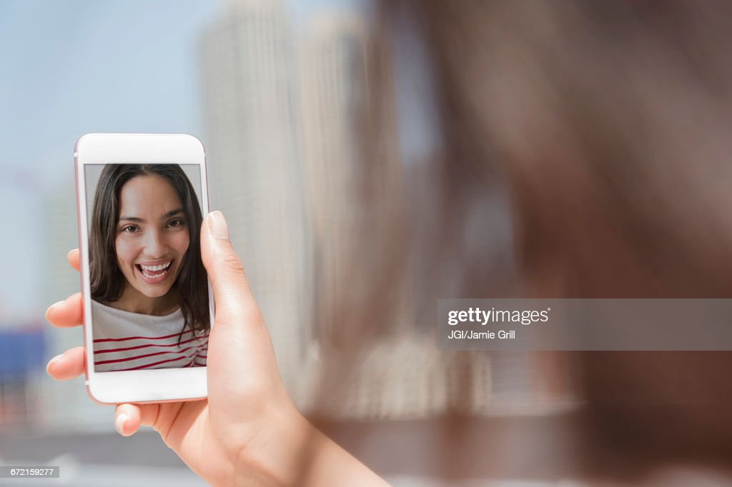 Smiling Hispanic woman posing for cell phone selfie : Stock Photo