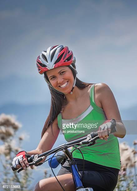 Smiling Hispanic woman posing on bicycle