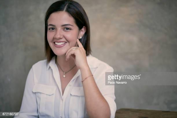Smiling Hispanic woman sitting at wooden table