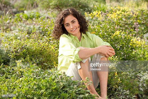 Smiling Hispanic woman sitting in garden