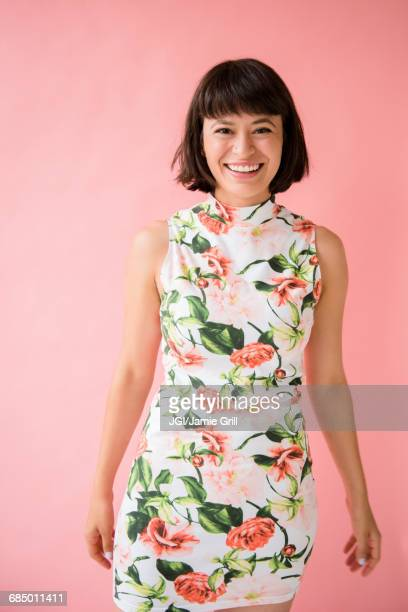 smiling hispanic woman wearing floral dress - kleid stock-fotos und bilder