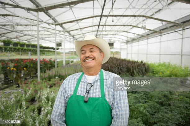 smiling hispanic worker standing in greenhouse - happy merchant stock pictures, royalty-free photos & images