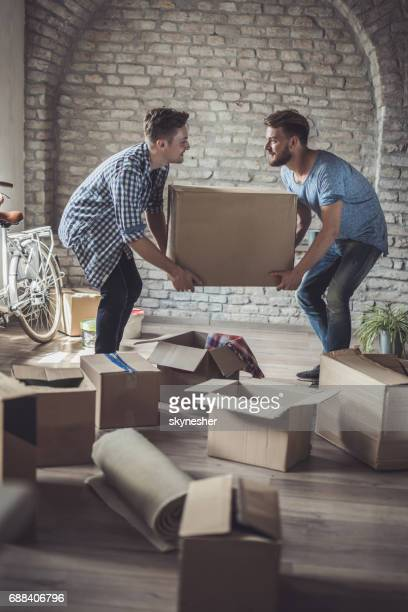 Smiling homosexual couple carrying cardboard box in their new home.