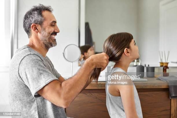 smiling homosexual father tying girl's hair - penteando imagens e fotografias de stock