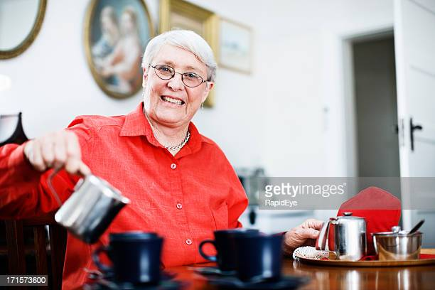Smiling, hospitable 70 year old woman pours tea or coffee
