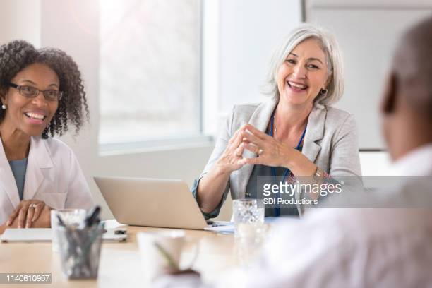 smiling hospital executive facilitates meeting - administrator stock pictures, royalty-free photos & images