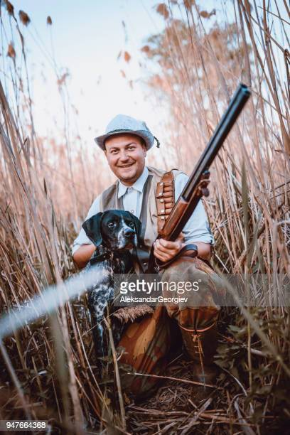 Smiling Hunter with his Dog Hiding in the Reed